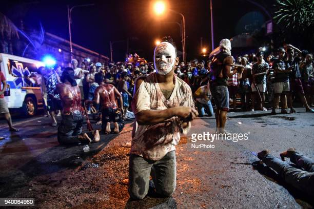 Masked flagellants with bloodied backs whip themselves during Good Friday Lenten rites in Navotas, Metro Manila, Philippines, March 30, 2018. Photo:...