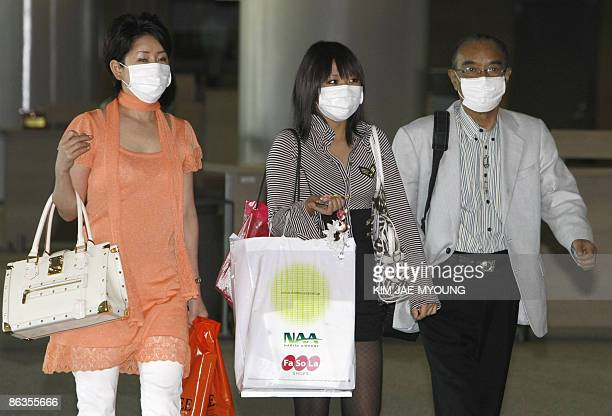 Masked foreign tourists arrive at Incheon International Airport west of Seoul on May 3 2009 South Korea reported a new probable case of swine flu...