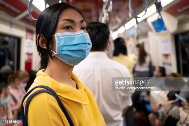 masked girl to protect herself from covid 19 virus in public area - covid-19 stock pictures, royalty-free photos & images