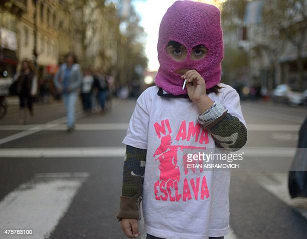 A masked girl wears a Tshirt reading 'Neither mistress nor slave' as she takes part in a demonstration against femicide under the slogan 'Not one...