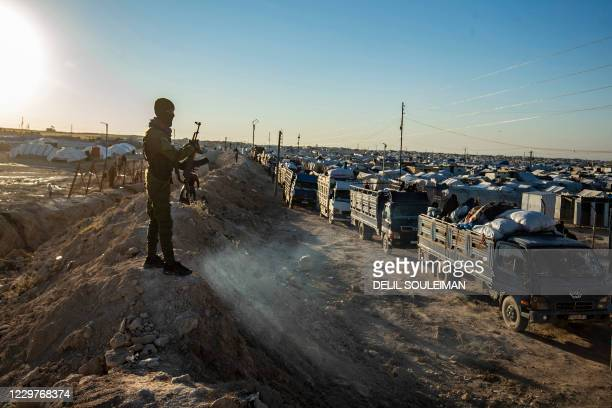 Masked guard keeps watch as trucks transports Syrians leaving the Kurdish-run al-Hol camp holding relatives of alleged Islamic State group fighters,...