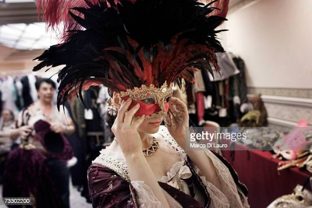 A masked guest tries a mask as she rents a costume at the Atelier Flavia at the Luna Hotel Baglioni to attend a party during the Carnival on February...