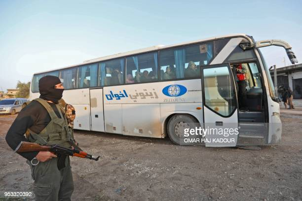 Masked gunman from Hayat Tahrir al-Sham stands guard as civilians who according to the Syrian Observatory of Human Rights were held hostage by...