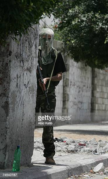 A masked gunman loyal to Fatah takes up a street position after clashes with Hamas gunmen June 11 2007 in Gaza City Gaza The latest fighting has been...