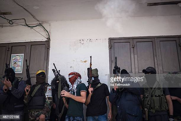 Masked gunmen fire during the funeral of Mohammed Lafi Abu Latifeh on July 27 2015 in Kalandia West Bank Mohammed was shot by Israeli security forces...
