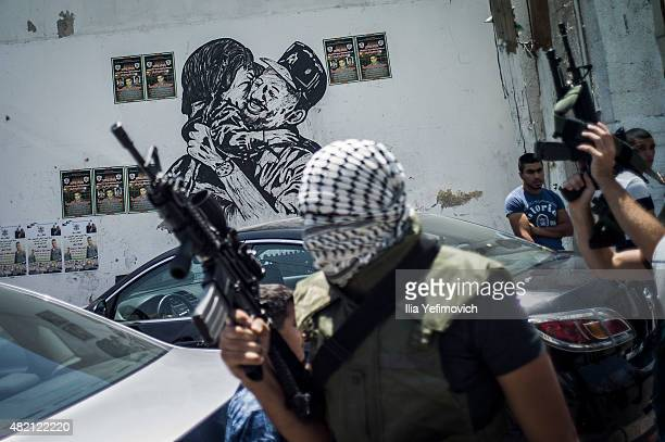 Masked gunmen seen during the funeral of Mohammed Lafi Abu Latifeh on July 27 2015 in Kalandia West Bank Mohammed was shot during an arrest by...