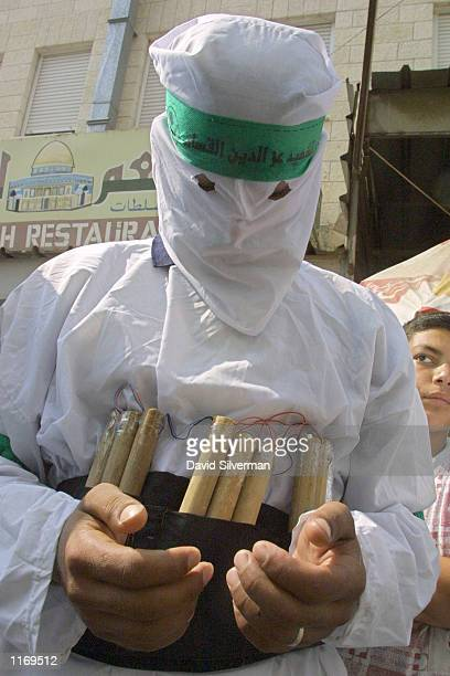 A masked Hamas militant dressed as a martyr prays while wearing a mock up of a suicidebomber's belt of explosives during the funeral of his slain...