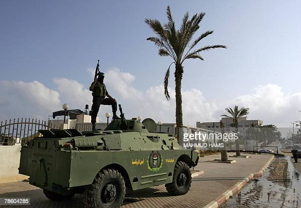 A masked Hamas militant stands on an armed vehicle belonging to Fatahaffiliated Force 17 presidential guard as he secures the seafront presidential...