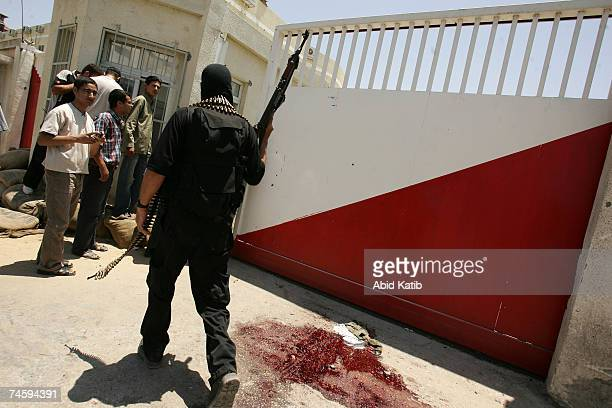 A masked Hamas militia gunman stands next a pool of blood after the killing of a member of the Preventative Security Force loyal to the Palestinian...