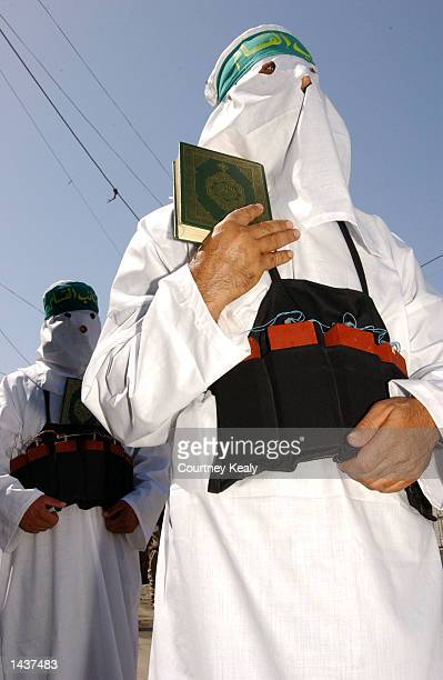 Masked Hamas supporters dressed as suicide bombers carry Korans as they march in a Hamas demonstration in Ain El Helweh Palestinian refugee camp...