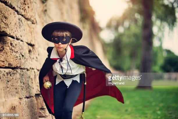 masked hero girl running to save the day - zorro foto e immagini stock