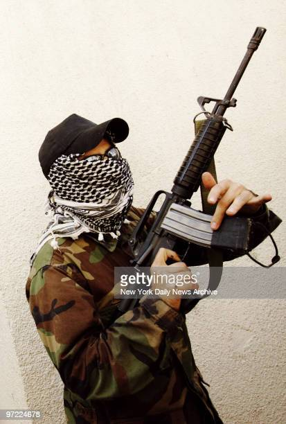 A masked Hezbollah fighter stands with an M4 rifle that he says was taken from a dead Israeli soldier in Aita Ech Chaab Lebanon on the first day of a...