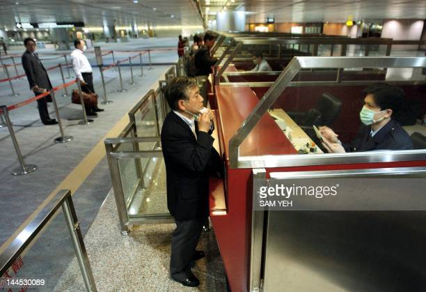 A masked immigration officer asks a passanger to take off his mask at a nearempty arrival hall at Chiang Kaishek International Airport at Taoyuan 10...