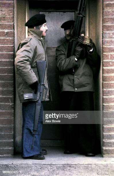 Masked IRA gunmen – one holding an Armalite rifle the other an M60 machine gun – crowd a doorway in the republican Creggan estate during a...