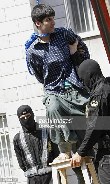Masked Iranian policemen help Hossein Kavousifar to stand on a stool before being hanged in public in central Tehran 02 August 2007 Two men convicted...