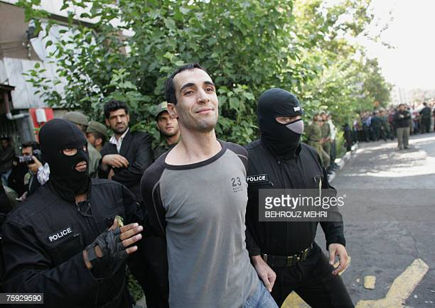 Masked Iranian policemen take Majid Kavousifar to the crime scene to hang him in public in central Tehran 02 August 2007 Two men convicted of...