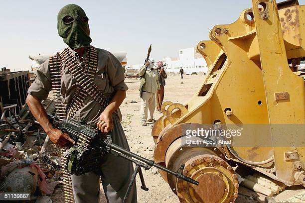 Masked Iraqi militiamen loyal to the radical Shiite cleric Moqtada al-Sadr, guard positions around al-Sadr's house on August 3, 2004 in the holy city...