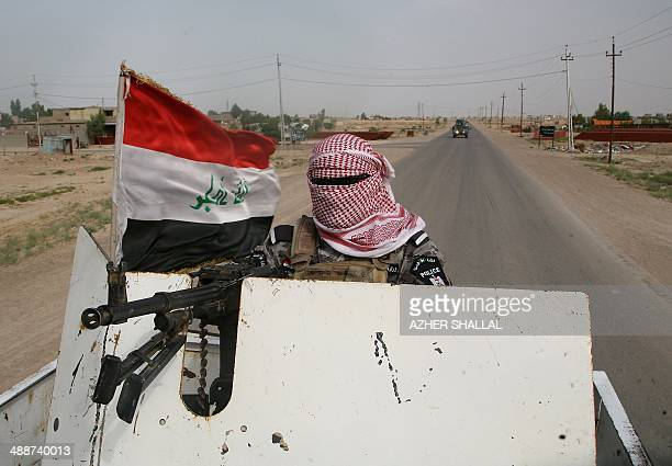 A masked Iraqi policeman handles a machine gun mounted on the back of a pick up truck during fighting against insurgents alongside local militiamen...