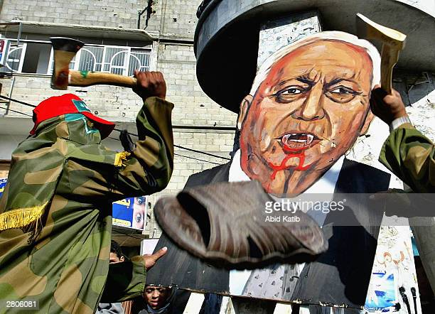 Masked Islamic Hamas militants attack an image of Israeli Prime Minister Ariel Sharon with axes during a rally to mark the 16th anniversary of Hamas'...