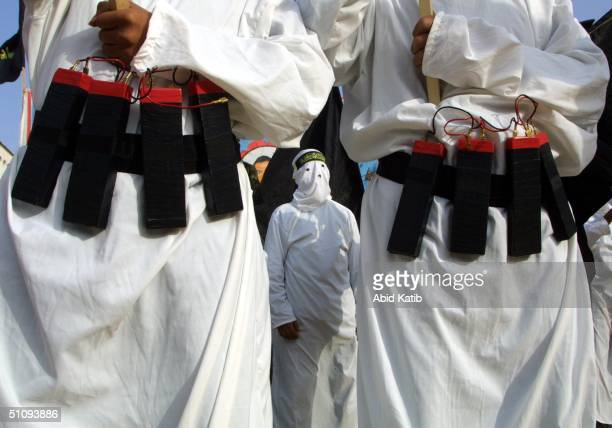 Masked Islamic Jihad Militants Wear Explosive Belts During A Rally Commemorating Mohammed Irhaem And Saleh Hassouna April 23 2002 In Gaza City Gaza...