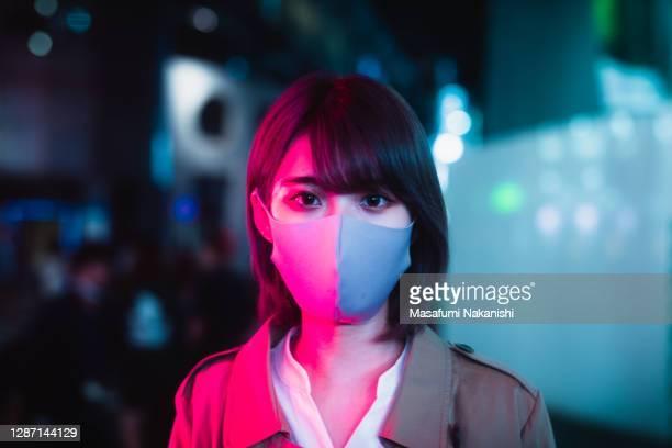 masked japanese woman standing in neon light of night street - 若い女性一人 ストックフォトと画像