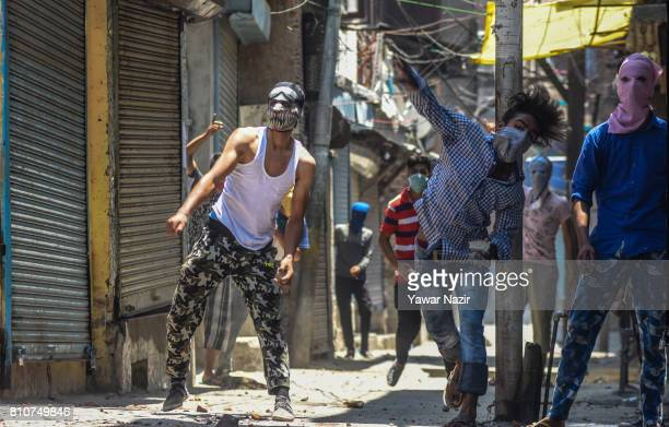 A masked Kashmiri Muslim protester throws a stone at Indian government forces during a protest after they defied curfew on the the first death...