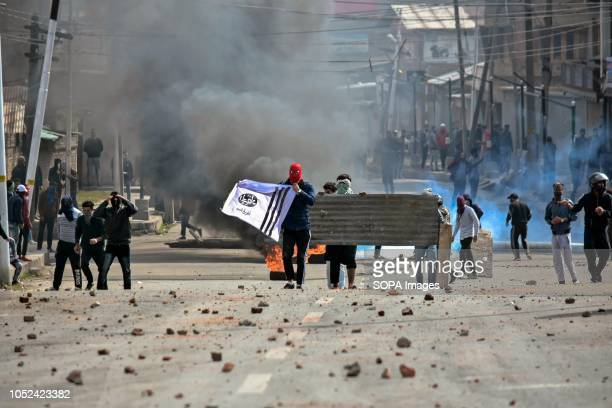 Masked Kashmiri protesters are seen holding a banner during the clashes Clashes broke out between militants and government forces in Srinagar The...