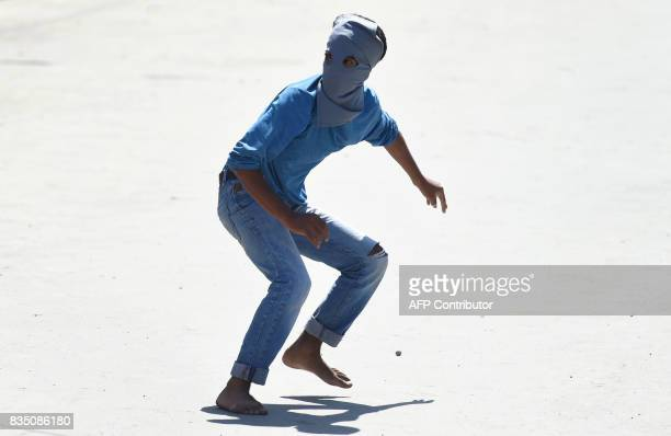 A masked Kashmiri protestor reacts after throwing stones towards Indian government forces during clashes after Friday congregational prayers outside...