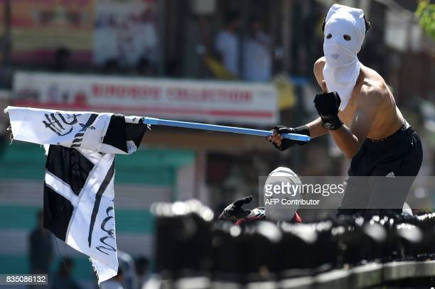 Masked Kashmiri protestors gesture towards Indian government forces during clashes after Friday congregational prayers outside The Jamia Masjid in...