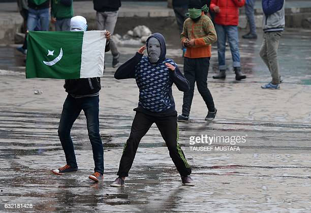 Masked Kashmiri protestors throw stones towards Indian government forces during clashes after Friday congregation prayers against Indian rule outside...
