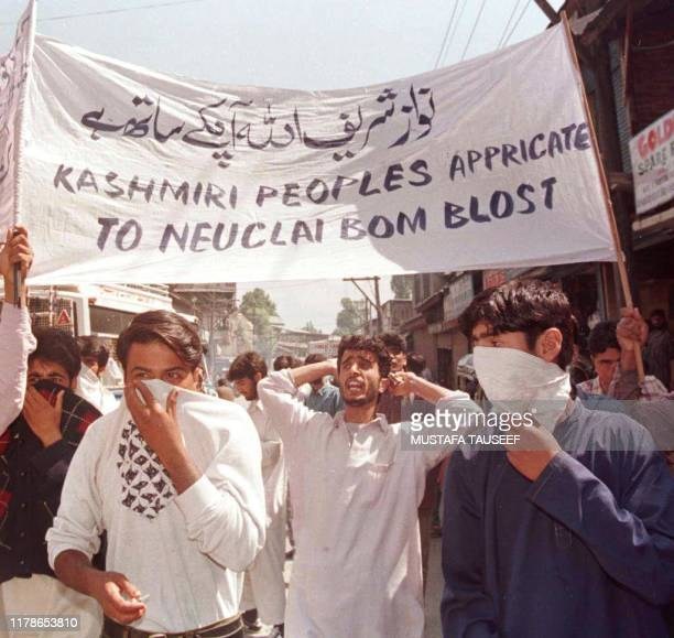 Masked Kashmiri youths hold a banner 01 June in appreciation of Pakistan's recent nuclear tests and let Nawaz Sharif know that god is with him. There...