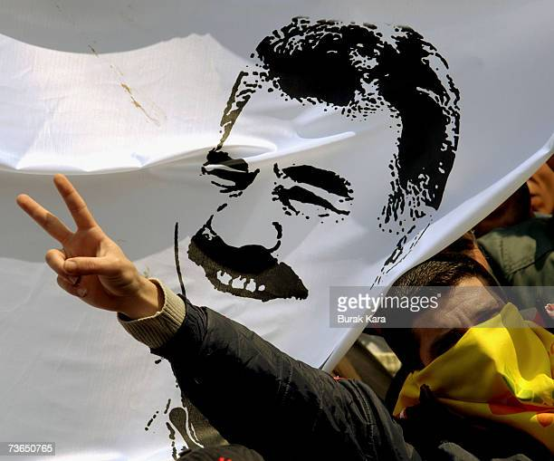 A masked Kurdish demostrator displays an image of jailed Kurdish rebel leader Abdullah Ocalan during a gathering to celebrate Newroz March 21 2007 in...