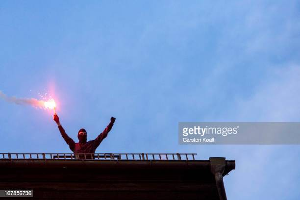 A masked leftwing protester holds a flare on the top of a building during a demonstration in Kreuzberg district on May Day on May 1 2013 in Berlin...