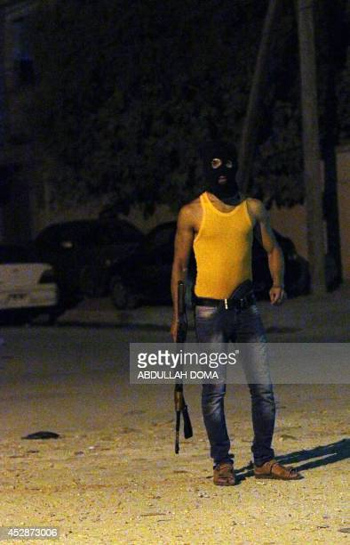 A masked Libyan gunman stands on a street in the eastern city of Benghazi early on July 29 as violence has hit the city cradle of the 2011 revolution...
