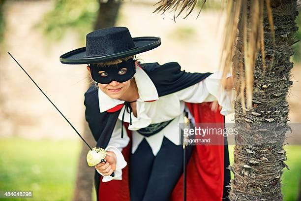 bambina dando mascherato eroe dietro palme - zorro foto e immagini stock