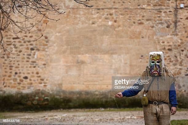 A masked man dressed as an Antruejo parades carrying cowbells tied to his back during the carnival of Carrizo de la Ribera in the northern Spanish...