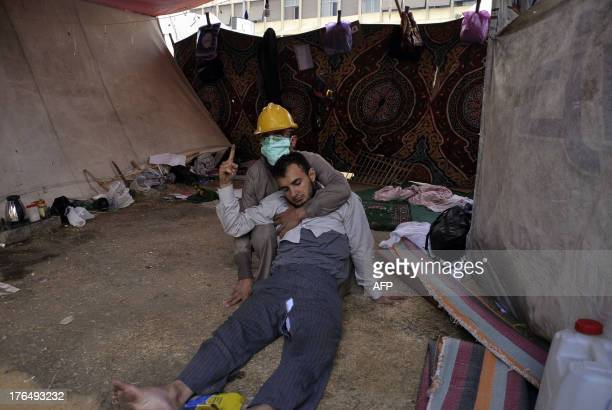 Masked man helps a wounded fellow protester inside a tent as Egyptian security forces move in to disperse supporters of Egypt's ousted president...