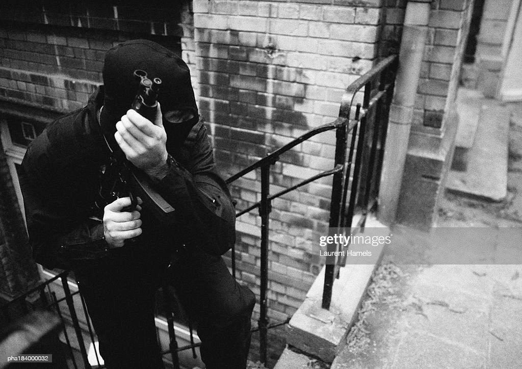 Masked man holding sub-machine gun, b&w : Stock-Foto