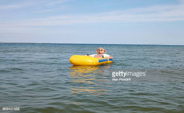 Masked man in blow up boat at sea