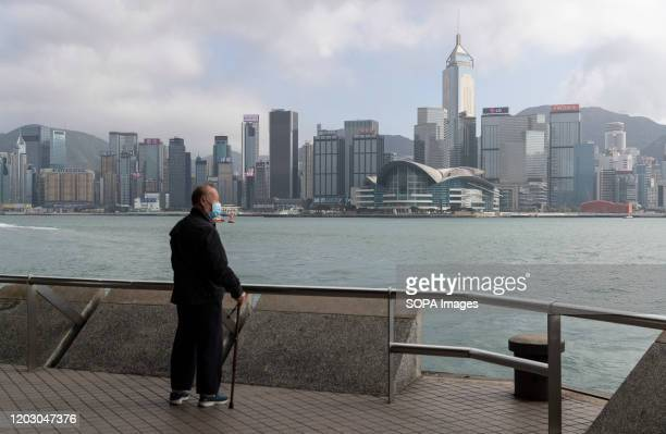 A masked man looking out Victoria Harbour in the very quiet and empty Tsim Sha Tsui Promenade one of the the top 10 Hong Kong attraction and normally...