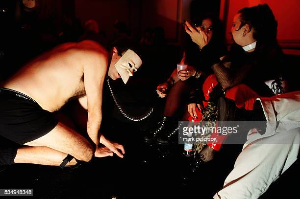 A masked man on a leash crouches next to two women during the Goddess Ball at the Palladium in Manhattan The Goddess Ball is a fetish drag queen and...