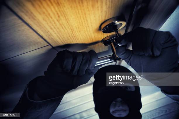 masked man opening the door - burglary stock pictures, royalty-free photos & images