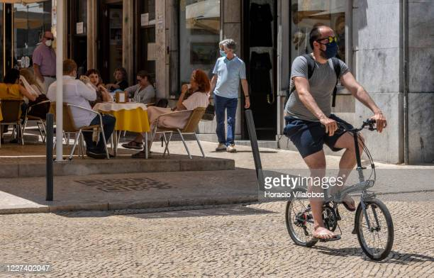 A masked man rides his bicycle past A Brasileira Cafe in Rua Garrett during the COVID19 Coronavirus pandemic on May 27 2020 in Lisbon Portugal Usage...