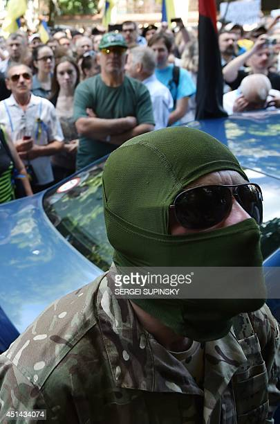 A masked man soldier of the volunteer Ukrainian army Donbass battalion takes part in a rally by Maidan activists at Independence Square in Kiev...