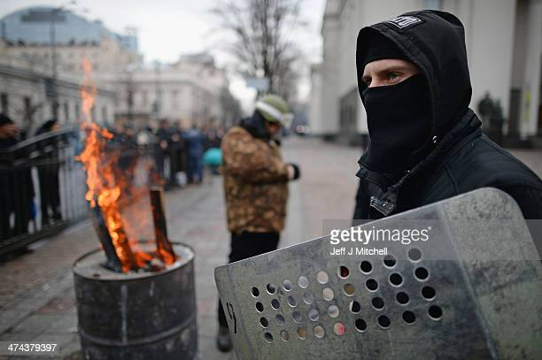 A masked man stands next to a fire outside the Ukrainian Parliament on February 23 2014 in Kiev Ukraine Prime Minister Yanukovych is said to have...