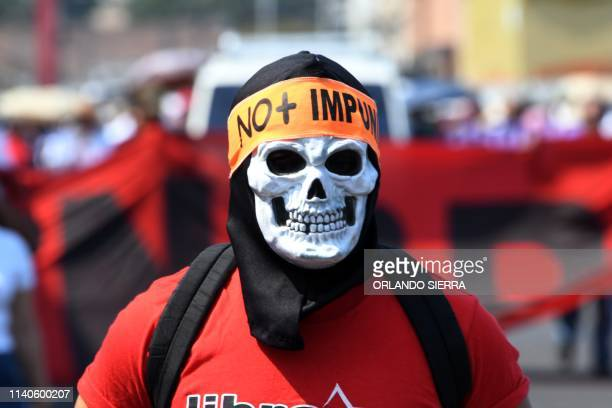 A masked man takes part in a May Day demonstration in Tegucigalpa on May 1 2019