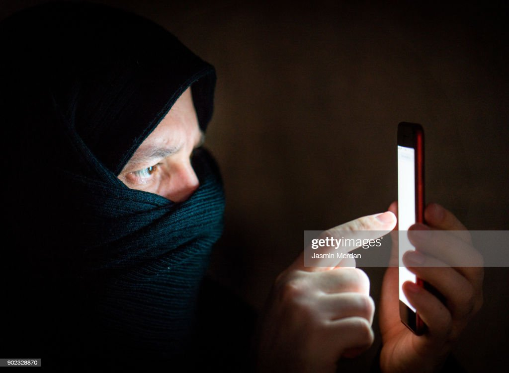 Masked man using smartphone ready for cyber attack : Stock Photo