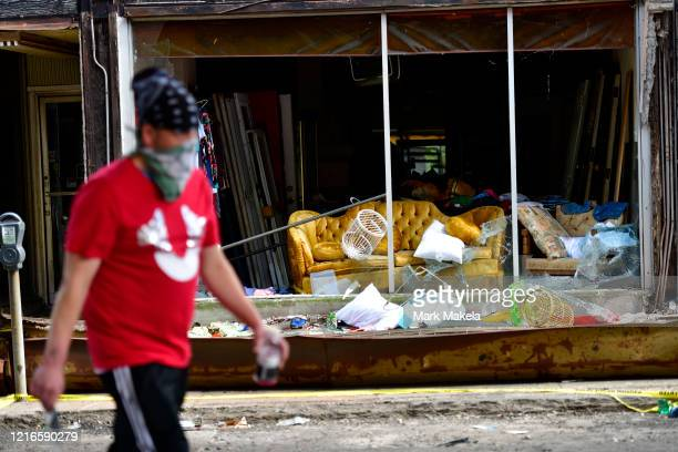 A masked man walks past a looted furniture store during a protest of the death of George Floyd on May 31 2020 in Philadelphia Pennsylvania Protests...