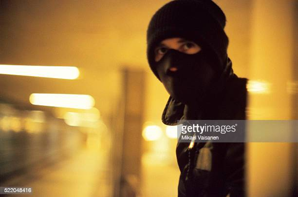 A masked man who is laying wait