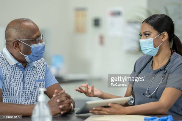 masked medical appointment - west indian culture stock pictures, royalty-free photos & images